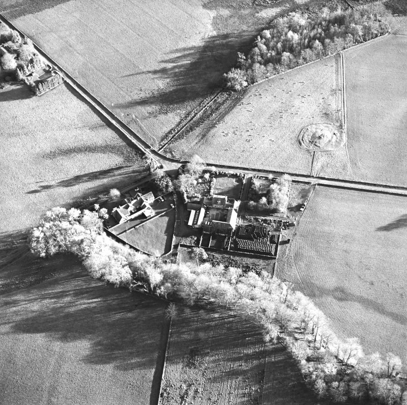 Oblique aerial view centred on the farmstead and school, with the remains of the cairn adjacent, taken from the NW.