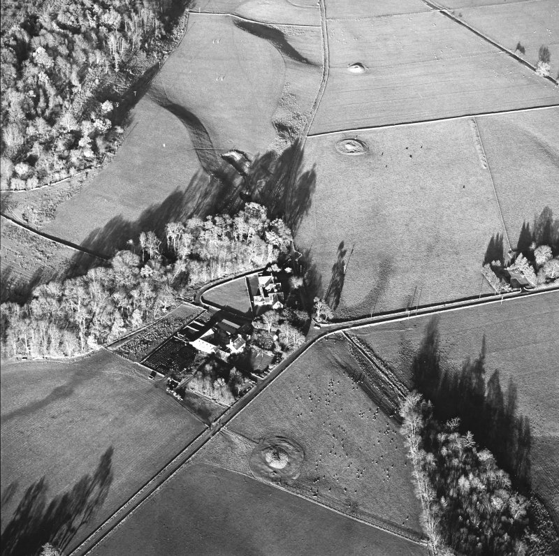 Oblique aerial view centred on the farmstead and school, with the remains of the cairns adjacent, taken from the SSW.