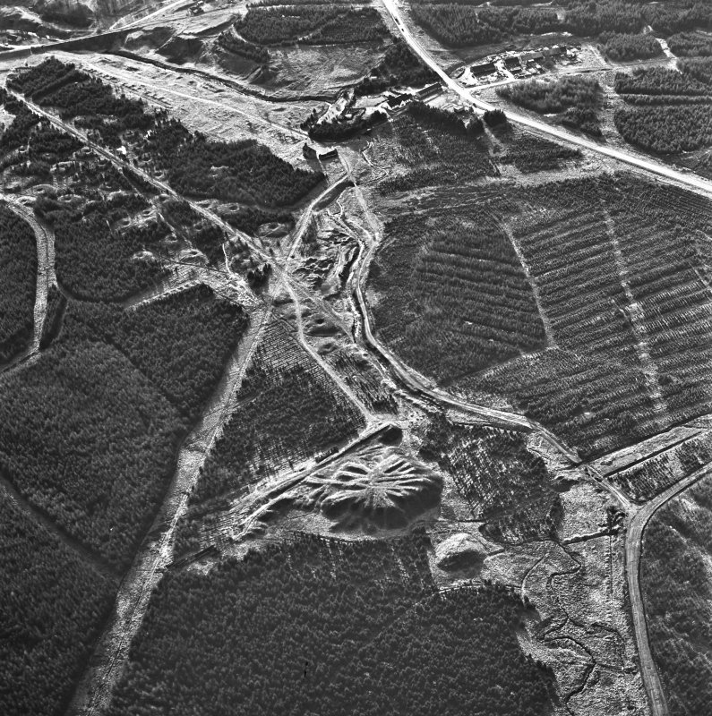 Wilsontown, oblique aerial view, taken from the NE, showing the bings of two coal mines at the bottom, and the remains of ironworks, workers' rows, lime kilns, coke ovens and buildings across the remainder of the photograph, including a large area of bell pits in the centre and top left-hand corner.