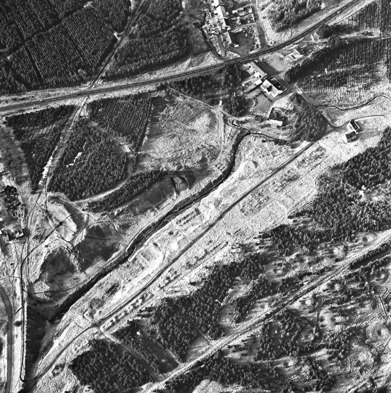 Wilsontown, oblique aerial view, taken from the SE, showing the the remains of ironworks, workers' rows, lime kilns, coke ovens, bell pits, and buildings across the photograph