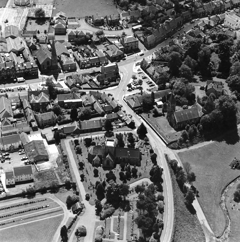 Oblique aerial view of Biggar centred on Biggar Church, churchyard, Moat Park Church and church hall, taken from the N.