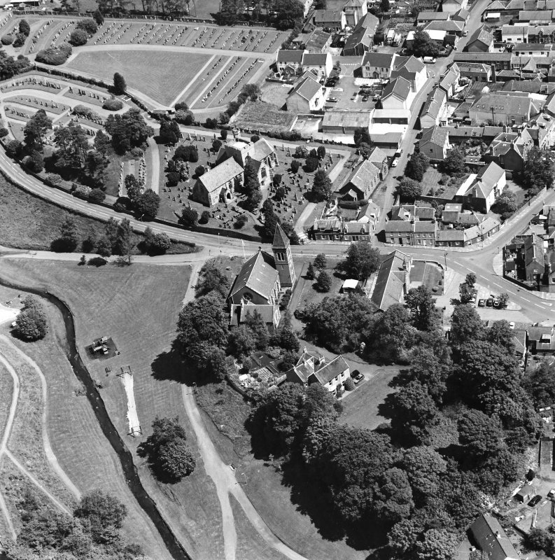 Oblique aerial view of Biggar centred on Biggar Church, churchyard and Moat Park Church, taken from the WSW.