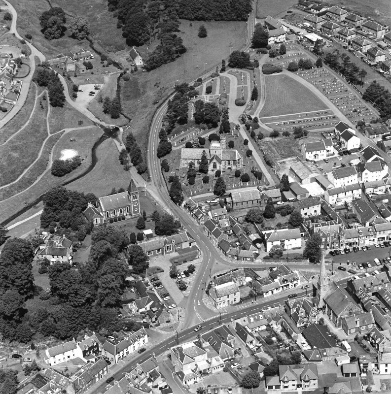 Oblique aerial view of Biggar centred on Biggar Church, churchyard, Moat Park Church and church hall, taken from the S.