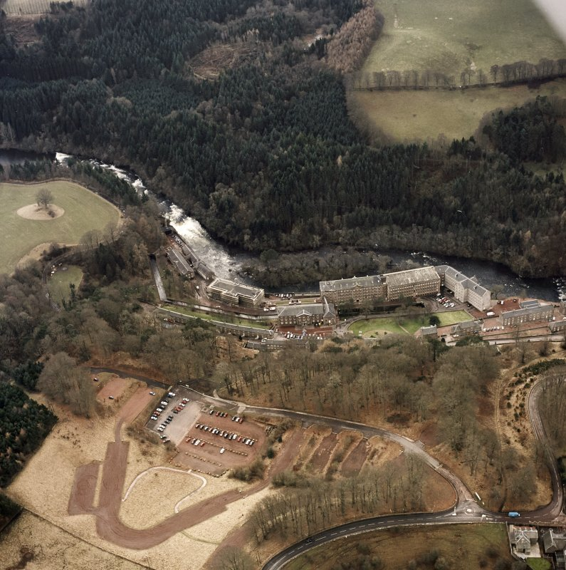 Oblique aerial view of New Lanark centred on the mills and schools, taken from the NE.