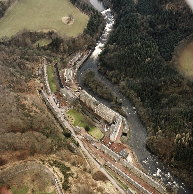 Oblique aerial view of New Lanark centred on the mills and schools, taken from the NNW.
