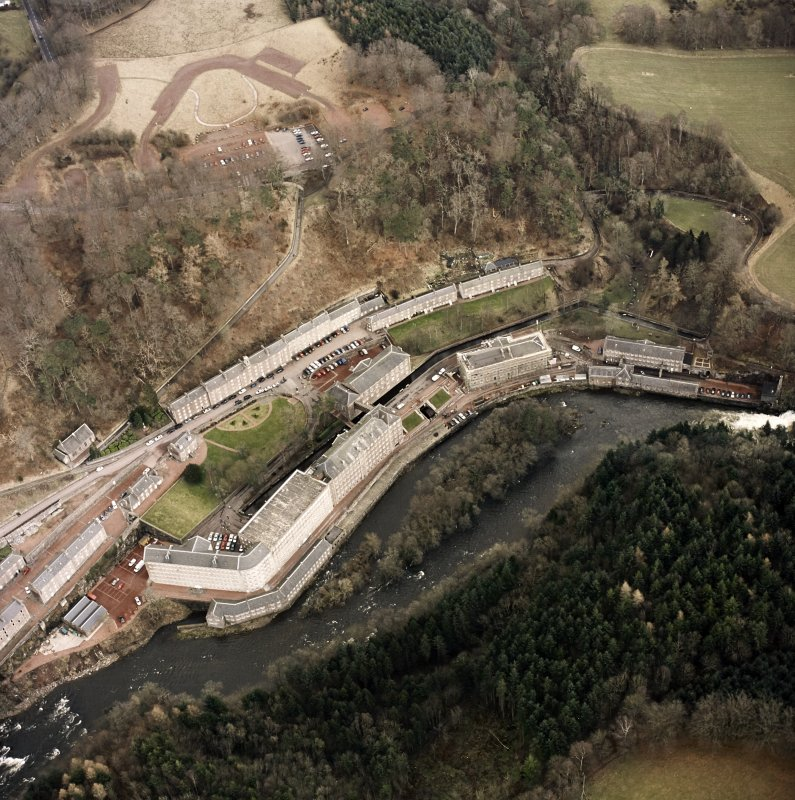 Oblique aerial view of New Lanark centred on the mills and schools, taken from the WSW.