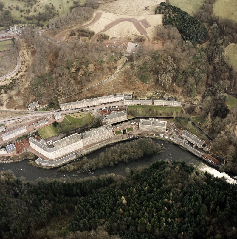 Oblique aerial view of New Lanark centred on the mills and schools, taken from the SW.