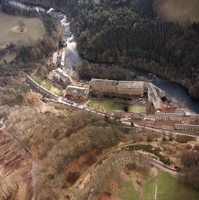 Oblique aerial view of New Lanark centred on the mills and schools, taken from the NNE.