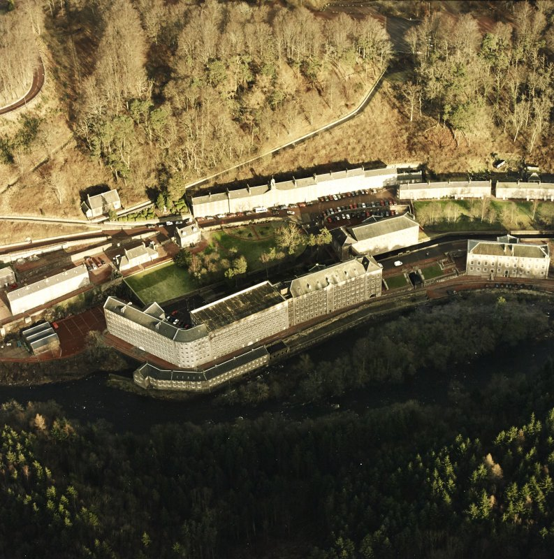 Oblique aerial view of New Lanark centred on the school and mills, taken from the SW.