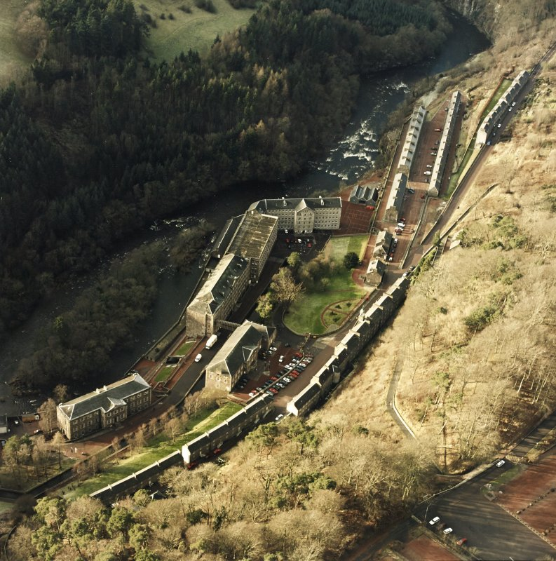 Oblique aerial view of New Lanark centred on the school and mills, taken from the ESE.
