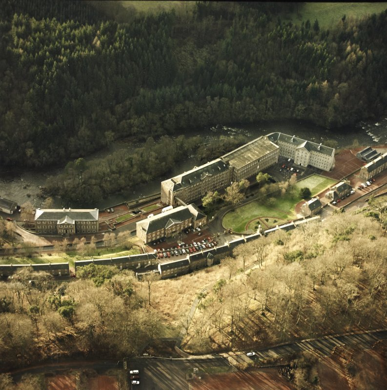 Oblique aerial view of New Lanark centred on the school and mills, taken from the ENE.