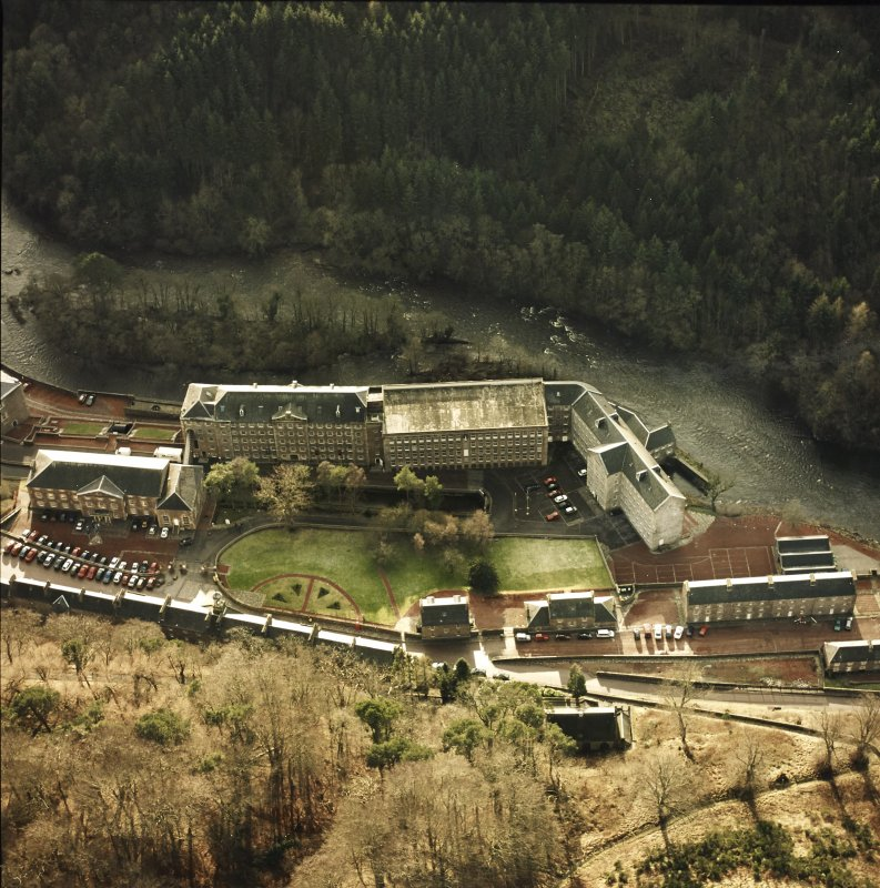 Oblique aerial view of New Lanark centred on the school and mills, taken from the NNE.