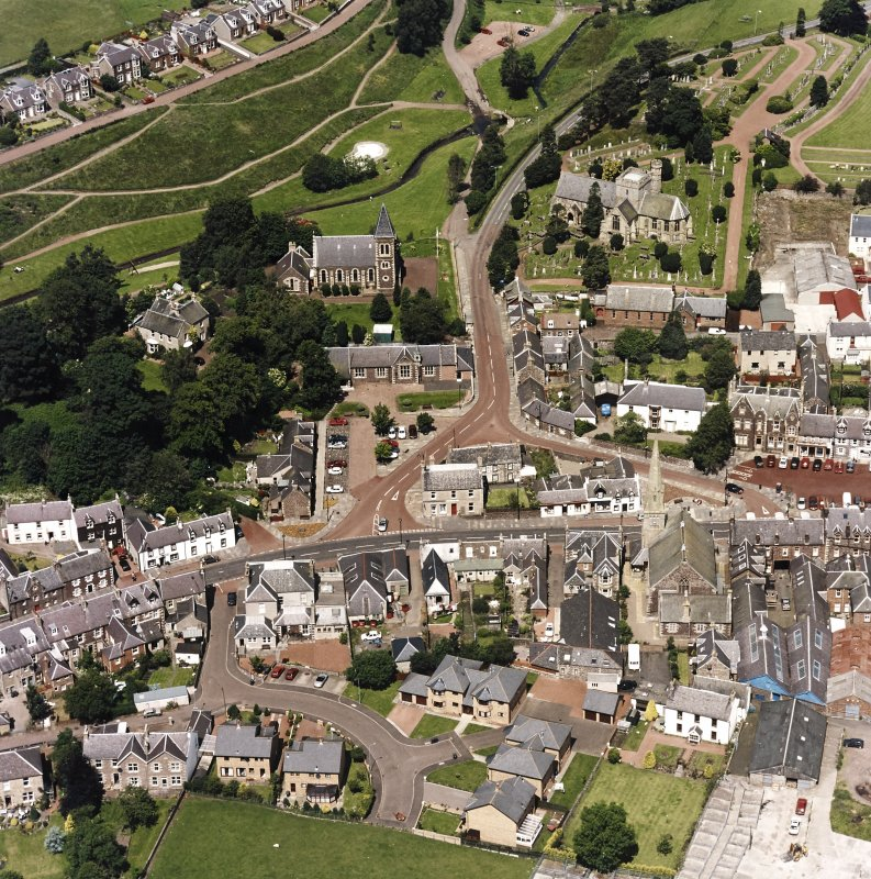 Oblique aerial view of Biggar centred on Biggar Church, churchyard, Moat Park Church and church hall, taken from the SSE.