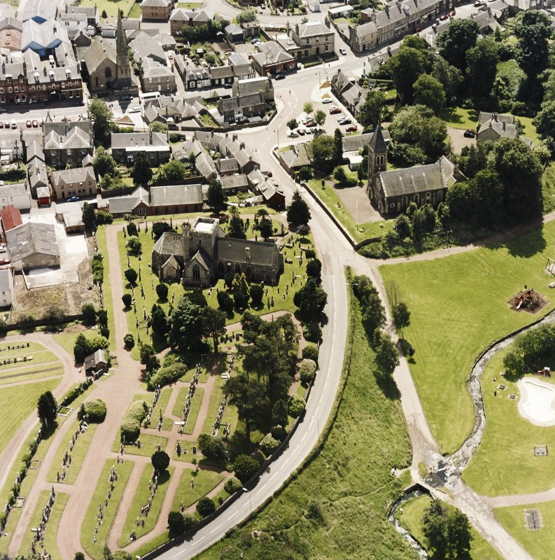 Oblique aerial view of Biggar centred on Biggar Church, churchyard and Moat Park Church, taken from the N.