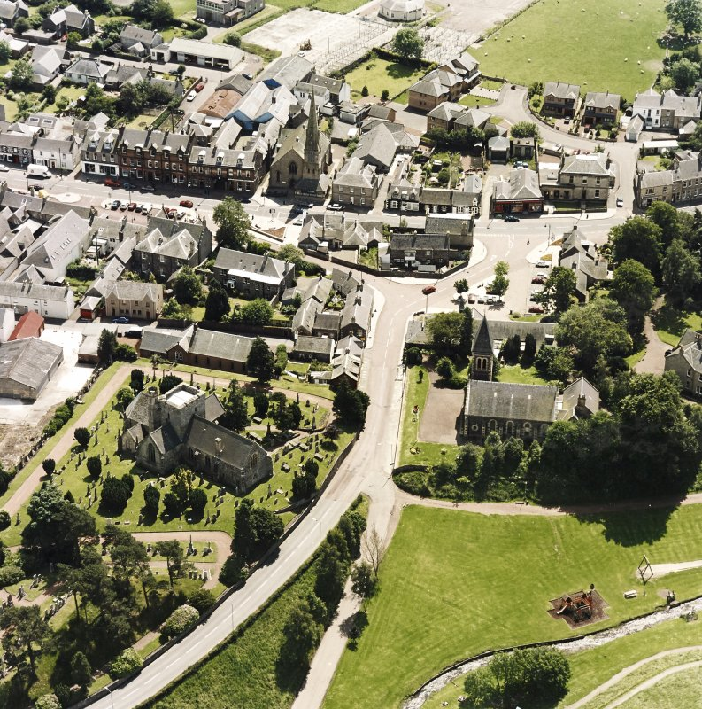 Oblique aerial view of Biggar centred on Biggar Church, churchyard, Moat Park Church and church hall, taken from the NNW.