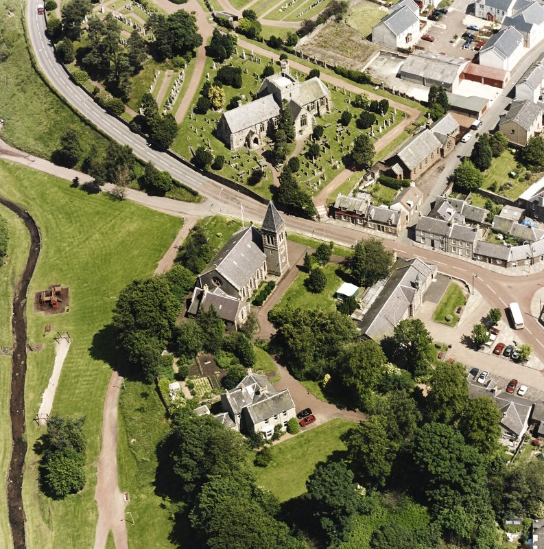 Oblique aerial view of Biggar centred on Biggar Church, churchyard and Moat Park Church, taken from the SW.