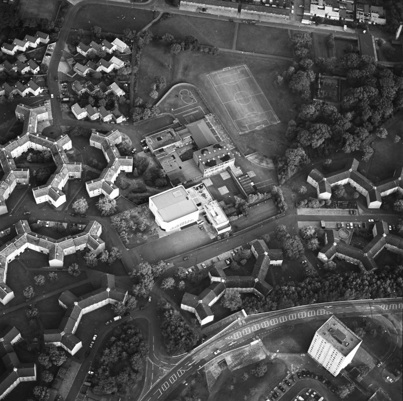 Oblique aerial view of Cumbernauld centred on sacred Heart Roman Catholic Church with the Sacred Heart Roman Catholic Primary School adjacent, taken from the NW and recorded as part of the World of Worship project.