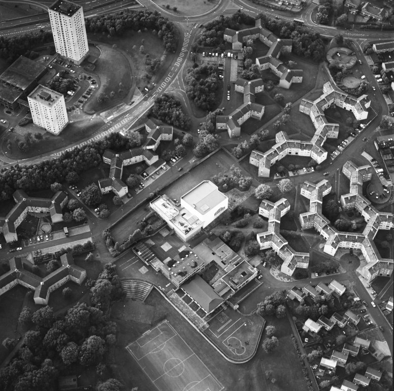 Oblique aerial view of Cumbernauld centred on sacred Heart Roman Catholic Church with the Sacred Heart Roman Catholic Primary School adjacent, taken from the SE and recorded as part of the World of Worship project.