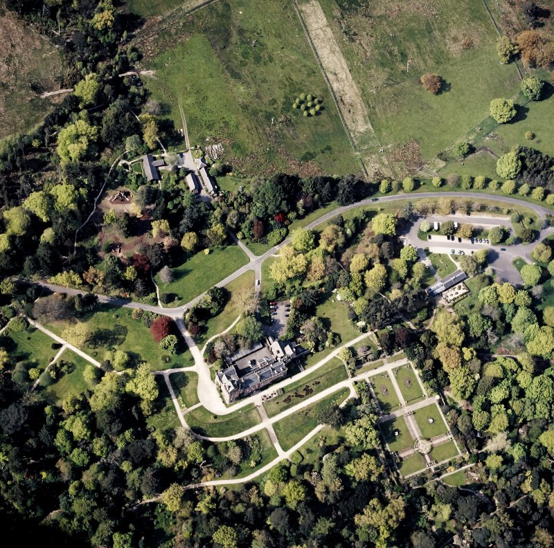 Oblique aerial view centred on the country house, walled garden and cottages, taken from the SSE.