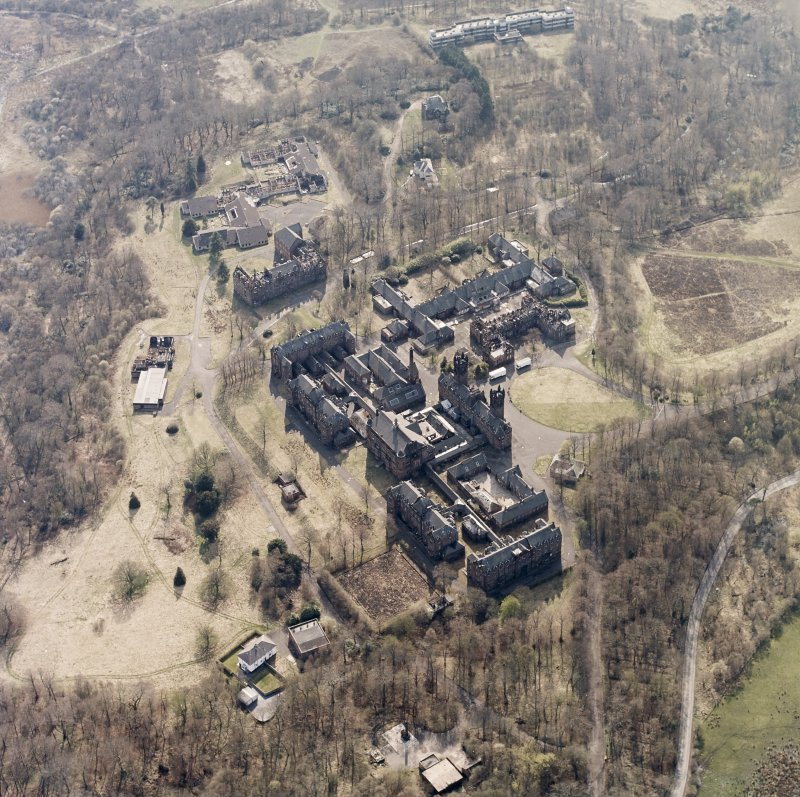 Oblique aerial view centred on the hospital, halls, nurses home, former mortuary, and workshops, taken from the ENE.