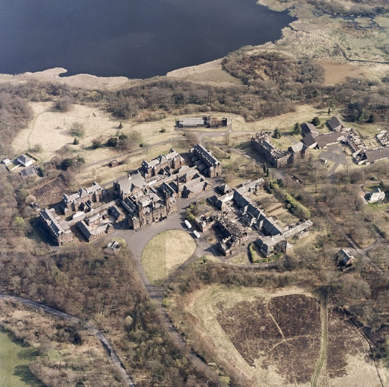 Oblique aerial view centred on the hospital, halls, nurses home, former mortuary, and workshops, taken from the NNW.