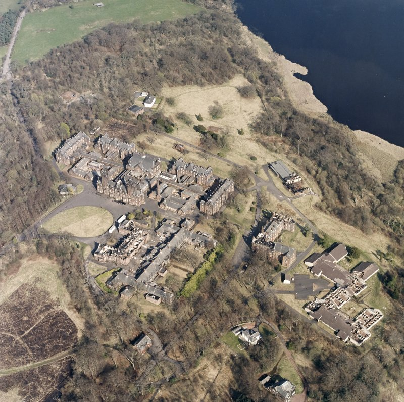Oblique aerial view centred on the hospital, halls, nurses home, former mortuary, and workshops, taken from the WSW.