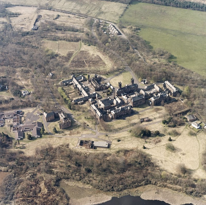 Oblique aerial view centred on the hospital, halls, nurses home, former mortuary, and workshops, taken from the SE.
