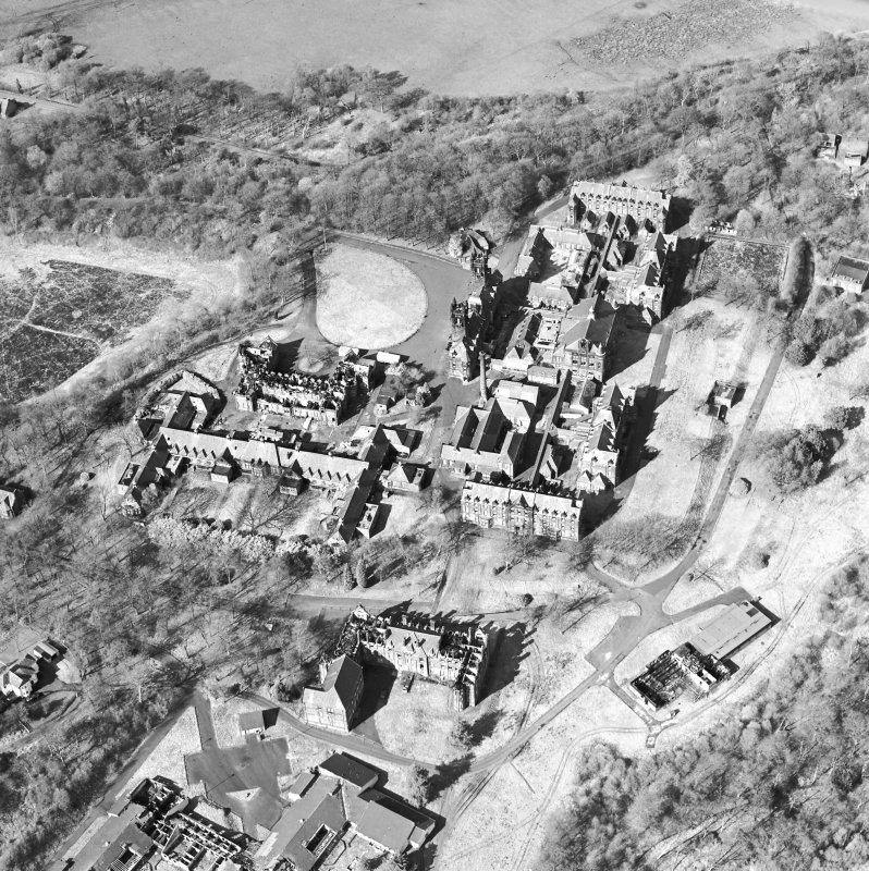 Oblique aerial view centred on the hospital, halls, nurses home, former mortuary, and workshops, taken from the SSW.