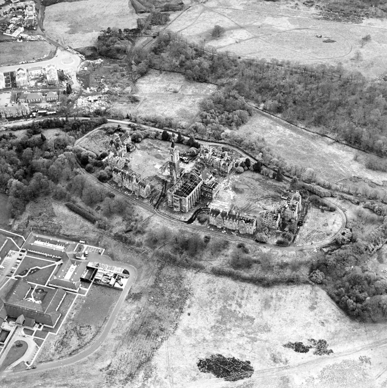 Oblique aerial view centred on the hospital partly under demolition, taken from the NNE.