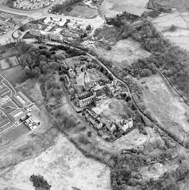 Oblique aerial view centred on the hospital partly under demolition, taken from the NNW.