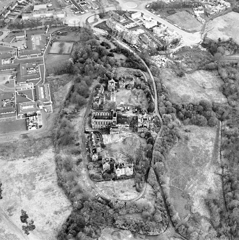 Oblique aerial view centred on the hospital partly under demolition, taken from the NW.