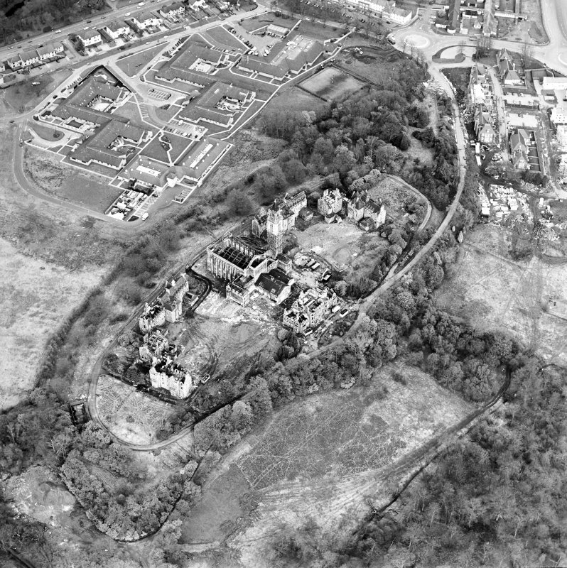 Oblique aerial view centred on the hospital partly under demolition, taken from the WNW.
