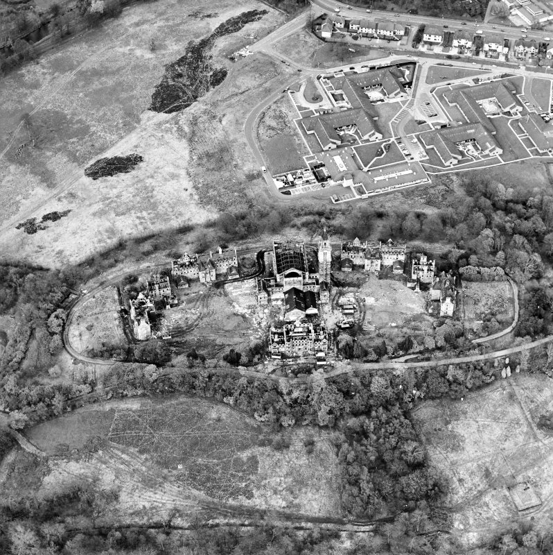 Oblique aerial view centred on the hospital partly under demolition, taken from the SSW.