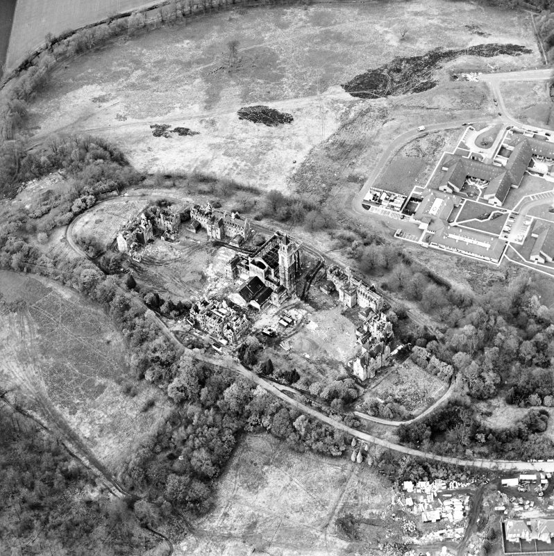 Oblique aerial view centred on the hospital partly under demolition, taken from the SW.