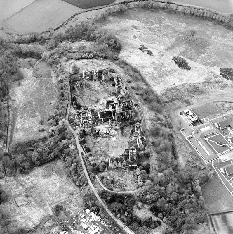 Oblique aerial view centred on the hospital partly under demolition, taken from the SE.