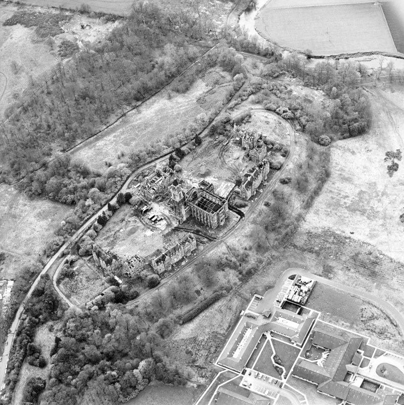 Oblique aerial view centred on the hospital partly under demolition, taken from the ENE.