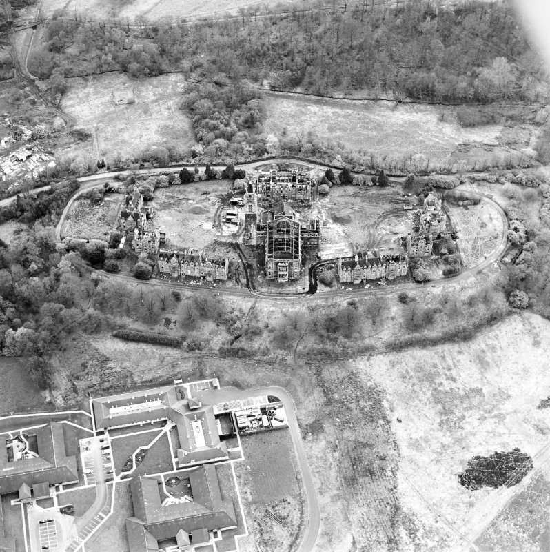 Oblique aerial view centred on the hospital partly under demolition, taken from the NE.