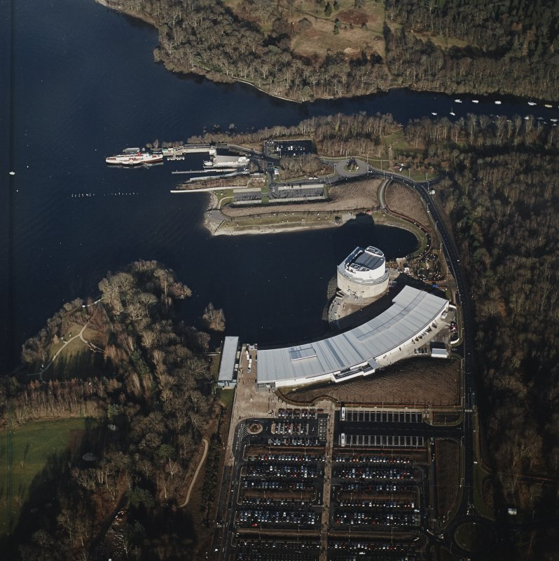 Oblique aerial view centred on the shopping centre and visitor centre with the pier and slipway adjacent, taken from the SW.