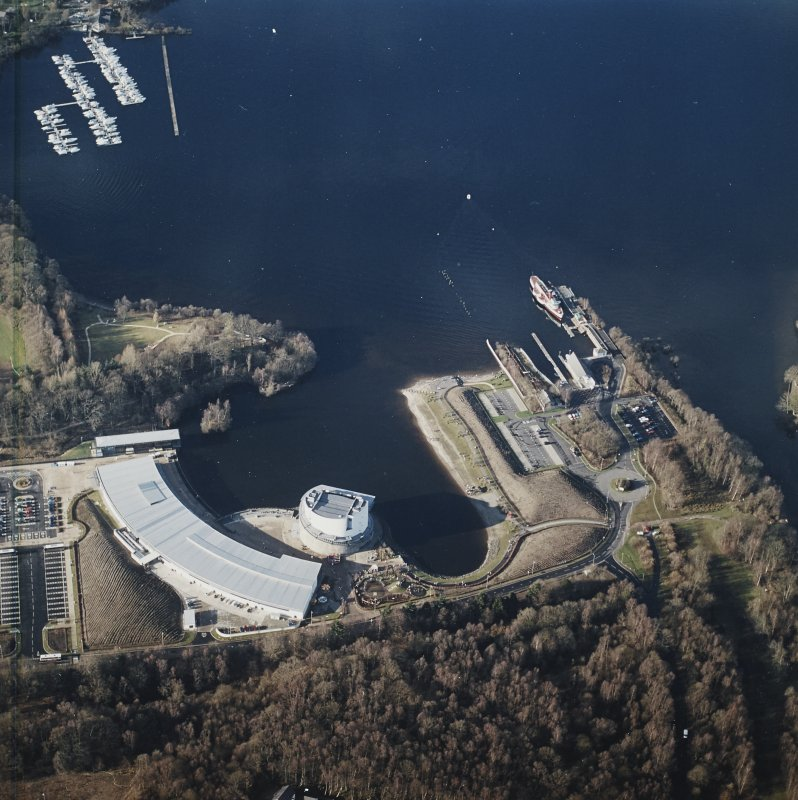 Oblique aerial view centred on the shopping centre and visitor centre with the pier and slipway adjacent, taken from the SE.