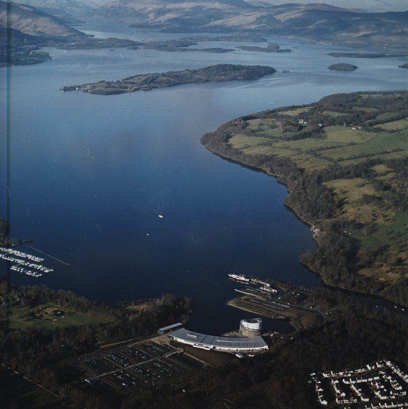 General oblique aerial view looking over the shopping centre, visitor centre, pier and slipway across Loch Lomond, taken from the SSW.