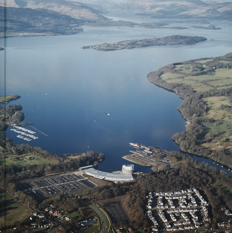 General oblique aerial view looking over the shopping centre, visitor centre, pier and slipway across Loch Lomond, taken from the S.