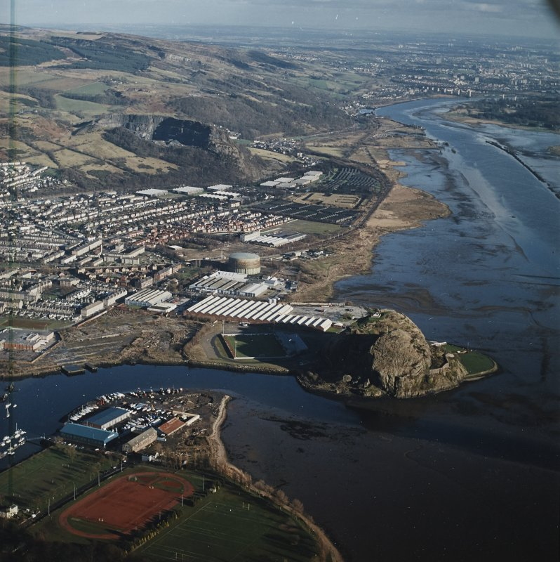 General oblique aerial view looking along the N bank of the River Clyde across the castle, fort, football ground, shipyard, works and the remains of the shipyard and works, taken from the W.