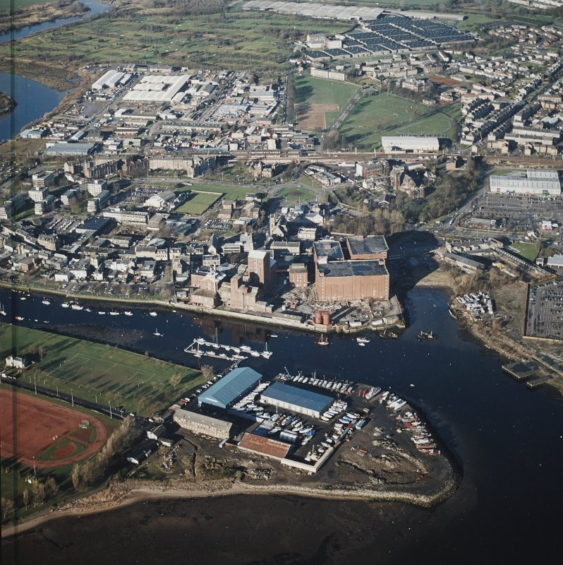 Oblique aerial view centred on the boat yard and whisky distillery, taken from the SSW.