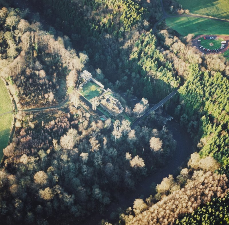 Oblique aerial view centred on the remains of the castle with the bridge adjacent, taken from the SE.