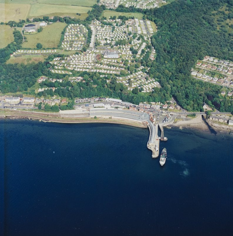 Oblique aerial view centred on the railway terminus, pier, farmsteading and the site of the country house, taken from the WNW.
