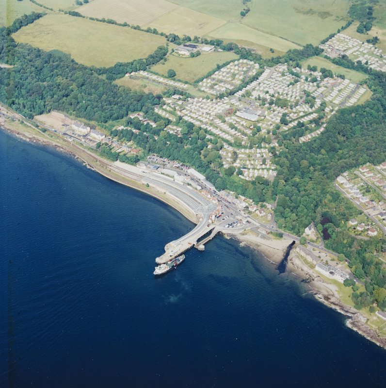 Oblique aerial view centred on the railway terminus, pier, farmsteading and the site of the country house, taken from the SW.