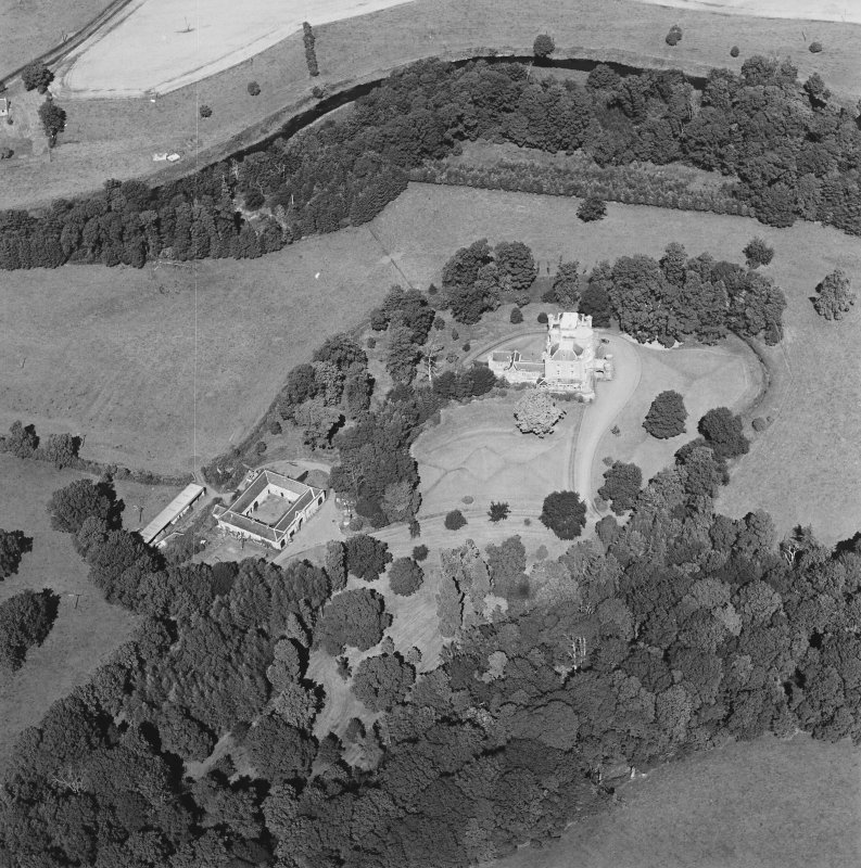 Oblique aerial view centred on the castle, tower-house and stables, taken from the SSW.