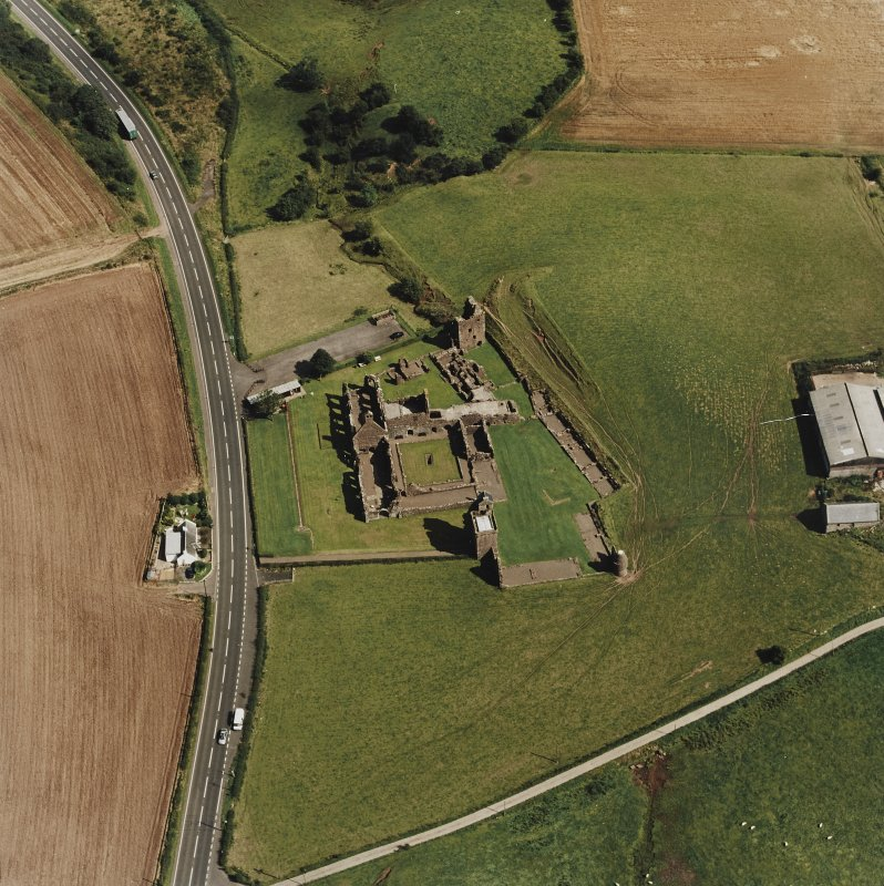 Oblique aerial view centred on the remains of the abbey and the doocot and cottage, taken from the W.