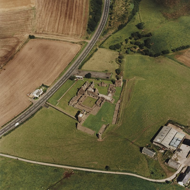 Oblique aerial view centred on the remains of the abbey and the doocot and cottage, taken from the SW.