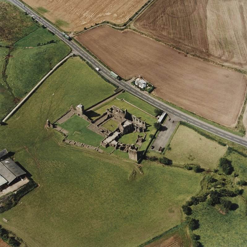 Oblique aerial view centred on the remains of the abbey and the doocot and cottage, taken from the ESE.
